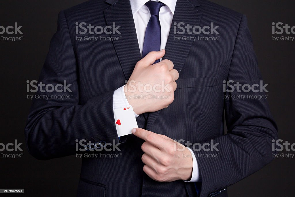 businessman with ace card hidden under sleeve stock photo