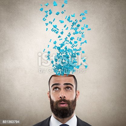 istock Businessman with alphabets emerging out from his head 831363794