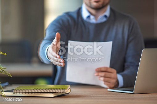 Businessman with an open hand ready for handshake - concept about agreement, partnership and win-win situation. Businessman  extending his arm in a handshake while sitting at his desk in an office