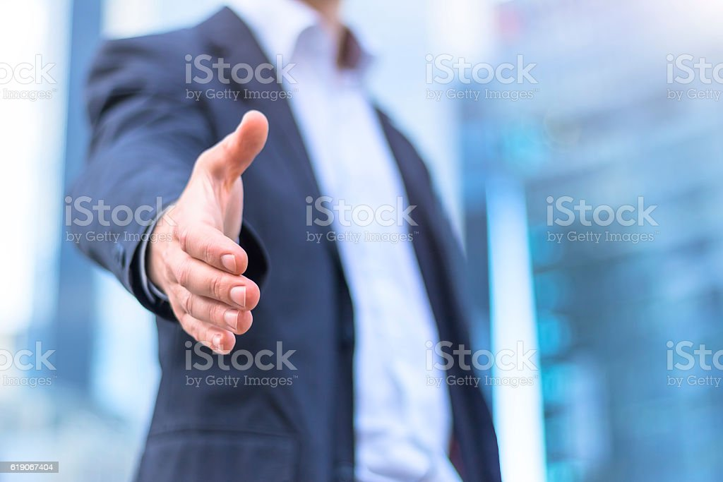 Businessman with an open hand ready for handshake - Photo