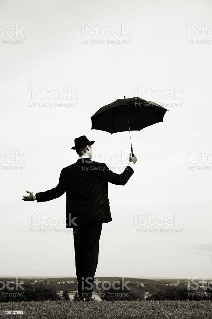 Businessman with an umbrella in field royalty-free stock photo