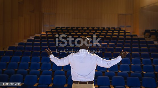 1133856033 istock photo Businessman with arm stretched out standing in a auditorium 1133851736