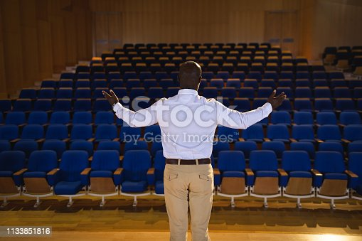 1133856033 istock photo Businessman with arm stretched out standing in a auditorium 1133851816