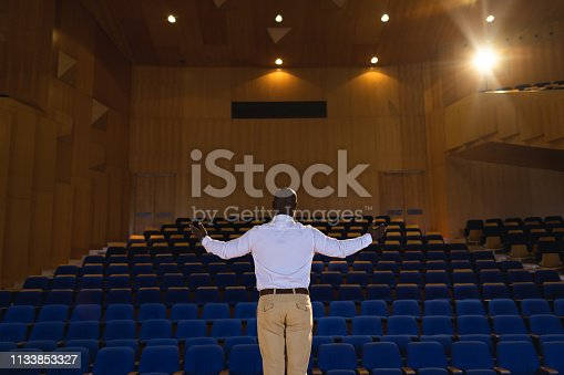 1133856033 istock photo Businessman with arm stretched out standing in a auditorium 1133853327