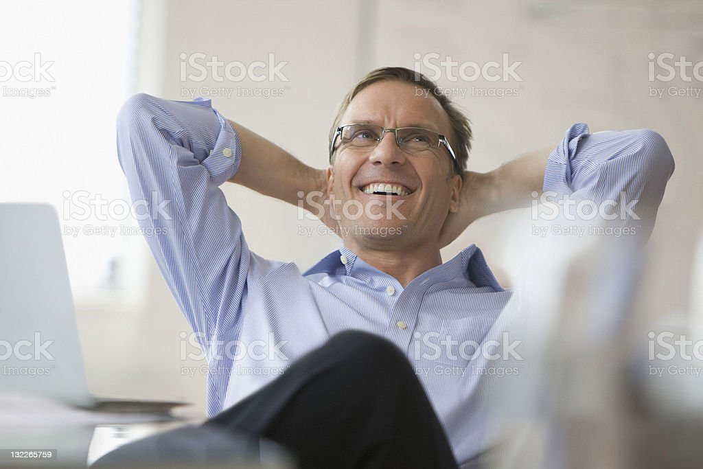 Businessman with arms behind his head stock photo