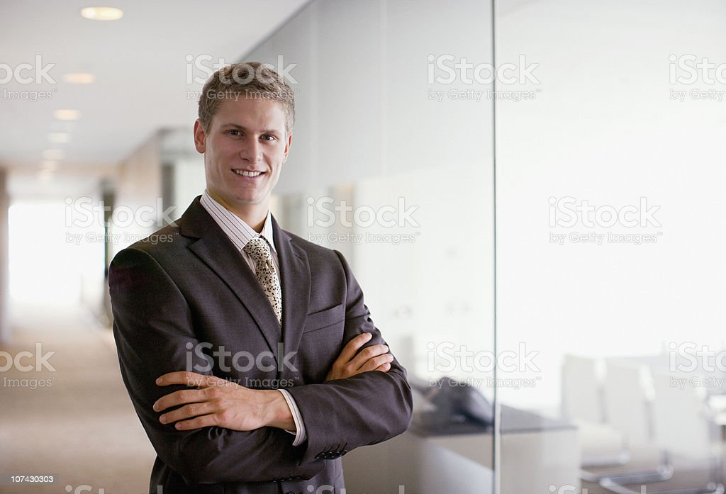 Businessman with arms crossed in office corridor stock photo