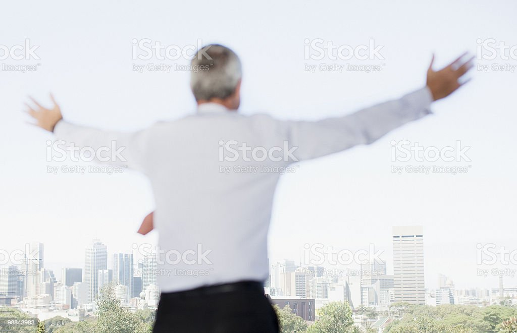 Businessman with arms outstretched on balcony royalty free stockfoto