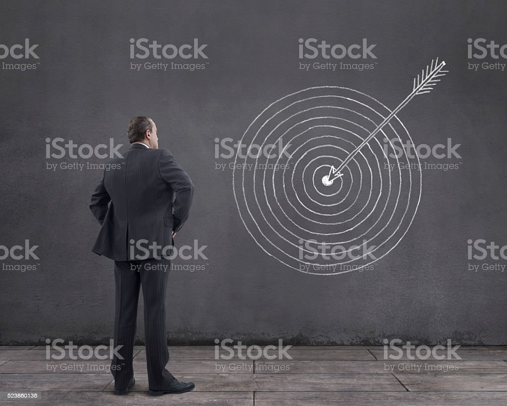 Businessman with Arrow Hits the Target Sketched on the Wall royalty-free stock photo