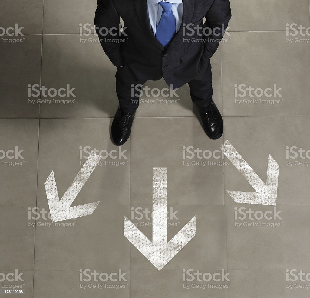 Businessman with arrows pointing in different directions stock photo
