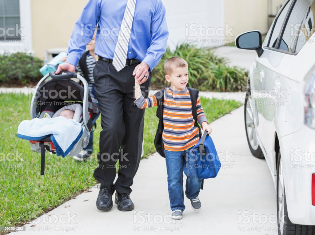 Businessman with baby taking son to school stock photo