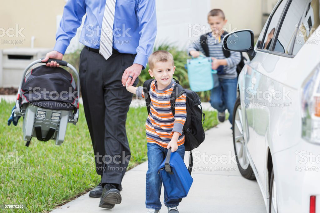 Businessman with baby taking sons to school stock photo