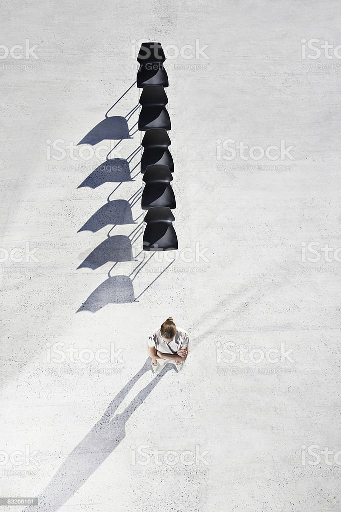 Businessman with back to line of office chairs royalty free stockfoto