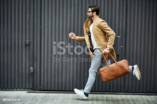 Full length of businessman running on sidewalk. Male professional is carrying bag by building. He is wearing smart casuals in city.