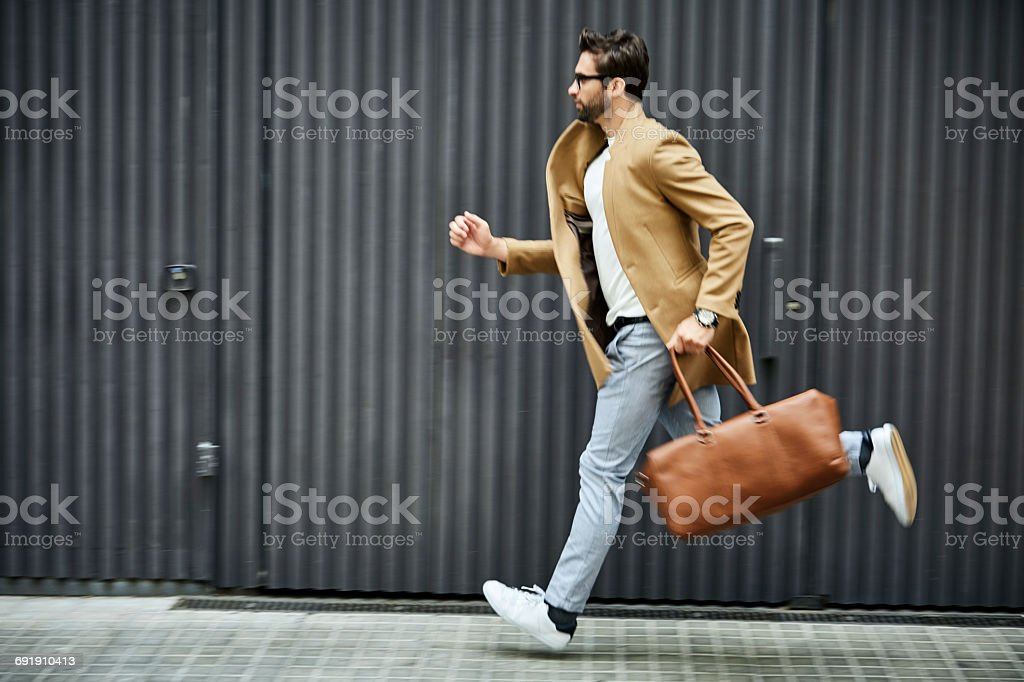 Businessman with bag running on sidewalk in city stock photo