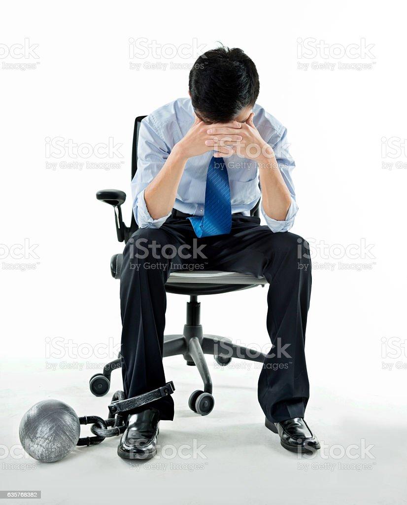 Hombre de negocios con bola de hierro y cadena contra un fondo blanco - foto de stock