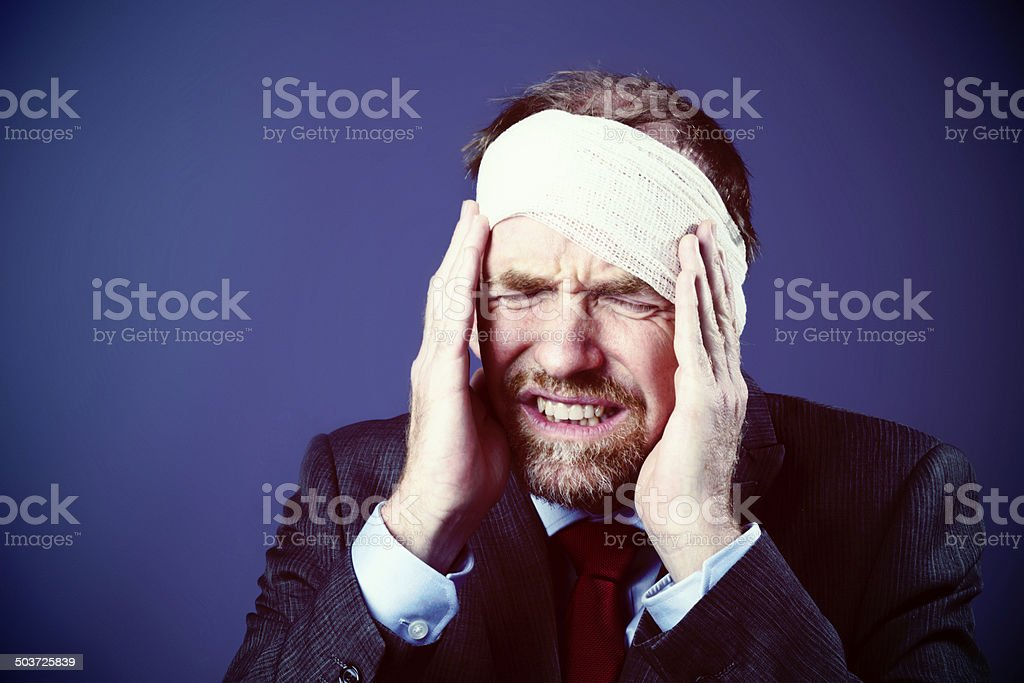 A mature businessman with his head wrapped in bandages, pressed his...