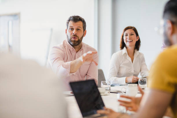 Businessman with beard explaining in meeting with colleagues