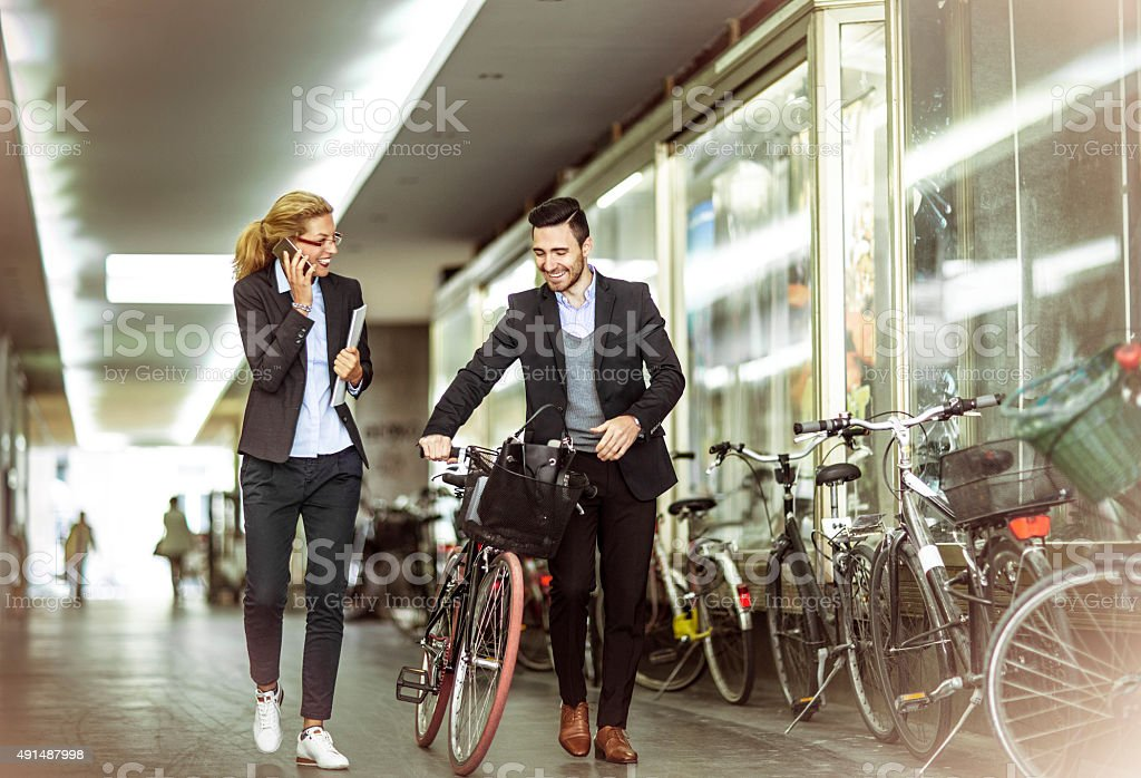 businessman with bicycle and  colleague walking on a city street stock photo