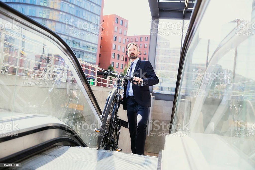 Businessman with bicycle moving on escalator stock photo