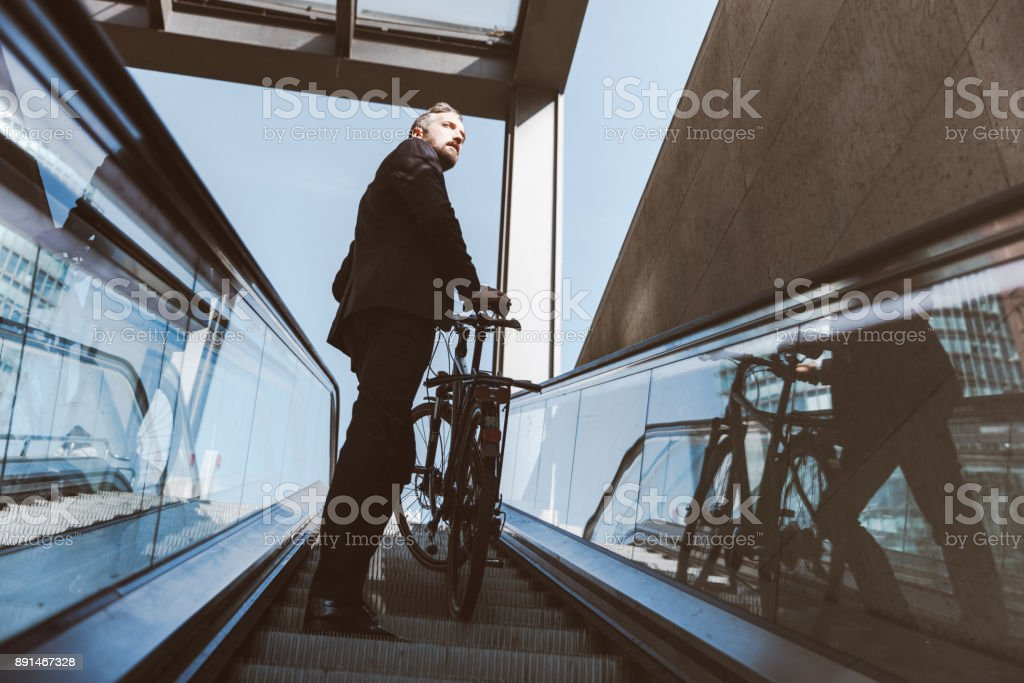 Businessman with bicycle on escalator stock photo