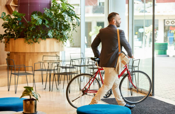 Businessman with bike going home after work stock photo