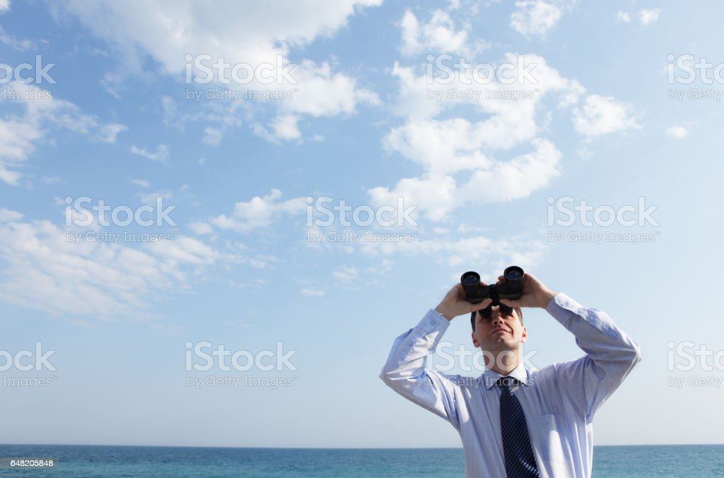 Businessman with binoculars Businessman with binoculars looking upward against a sea and skyscape 30-39 Years Stock Photo