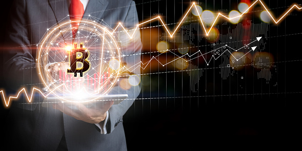 Businessman with Bitcoin currency and gold market exchange graphs