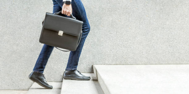 Businessman with black briefcase in hand walking up on stairs. Businessman with black briefcase in hand walking up on stairs. business goal, improvement, progress, Increase and growth concept. Outdoor closeup shot. in grey wall copy space. briefcase stock pictures, royalty-free photos & images