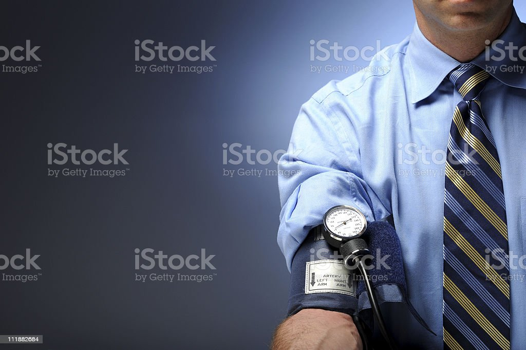 Businessman with blood pressure cuff on right arm stock photo