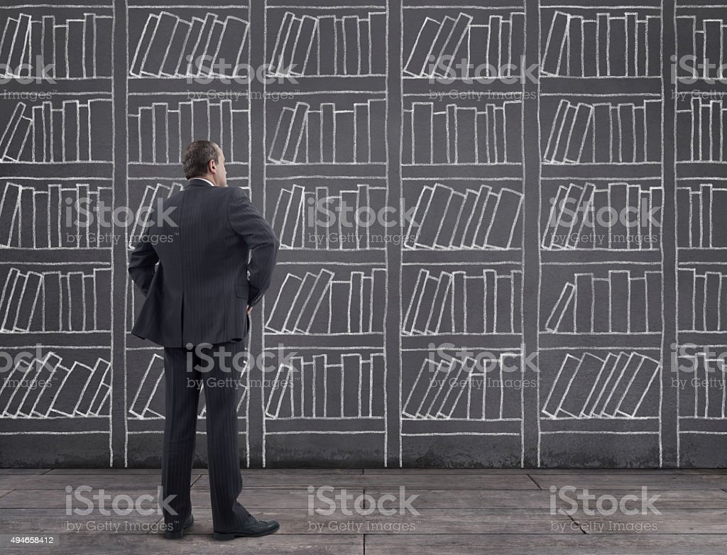 Businessman With Bookshelf Sketched On The Wall Royalty Free Stock Photo