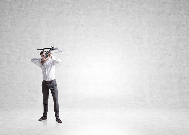 businessman with bow on concrete - crossbow stock pictures, royalty-free photos & images
