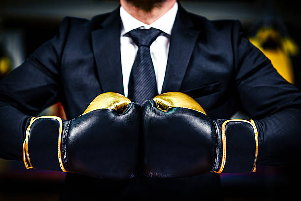 Businessman with boxing gloves is ready for corporate battle. stock photo
