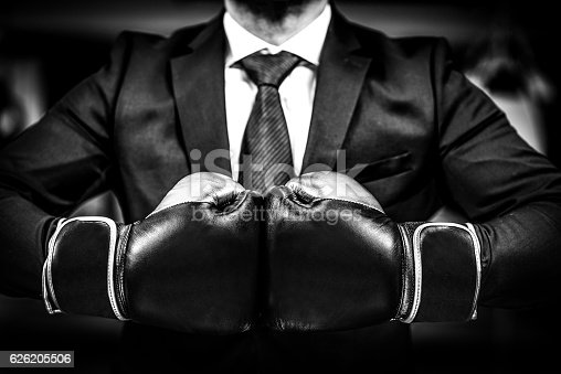 istock Businessman with boxing gloves is ready for corporate battle. 626205506