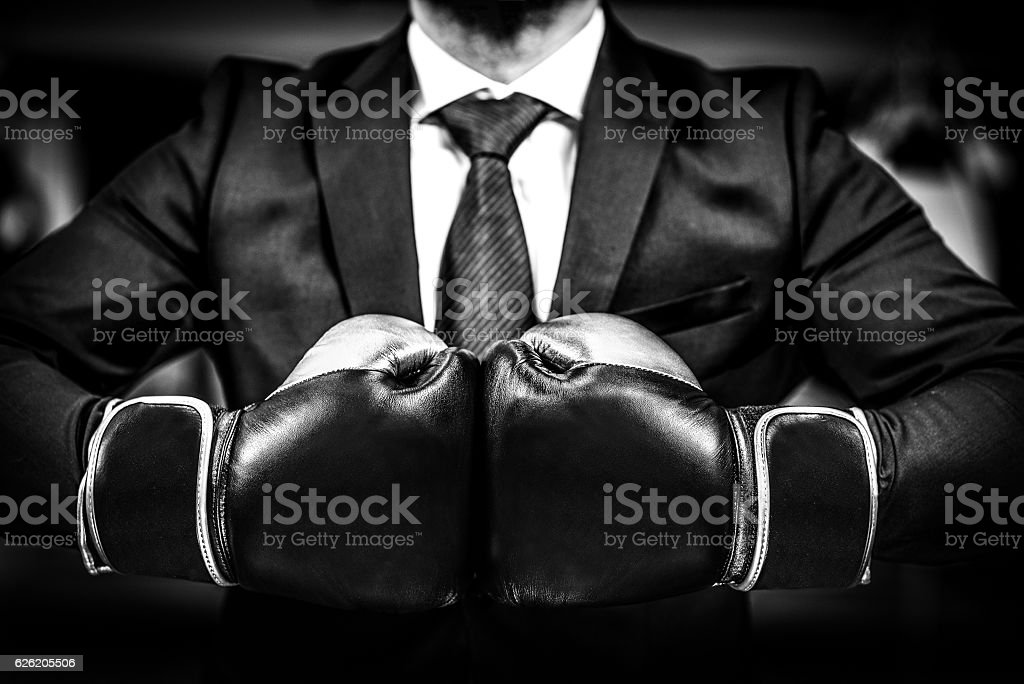 Businessman with boxing gloves is ready for corporate battle. - foto de stock