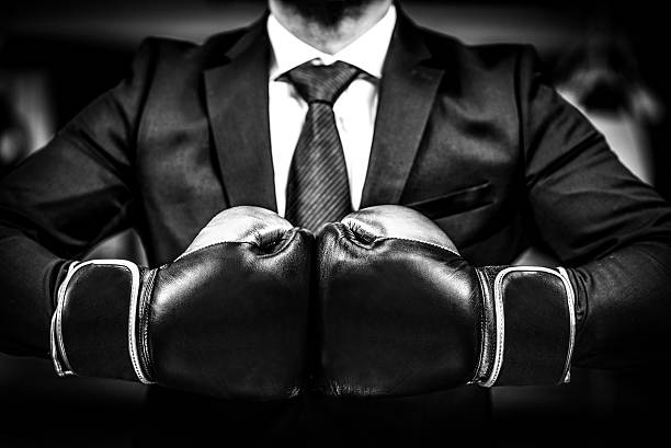 businessman with boxing gloves is ready for corporate battle. - aggression stock pictures, royalty-free photos & images