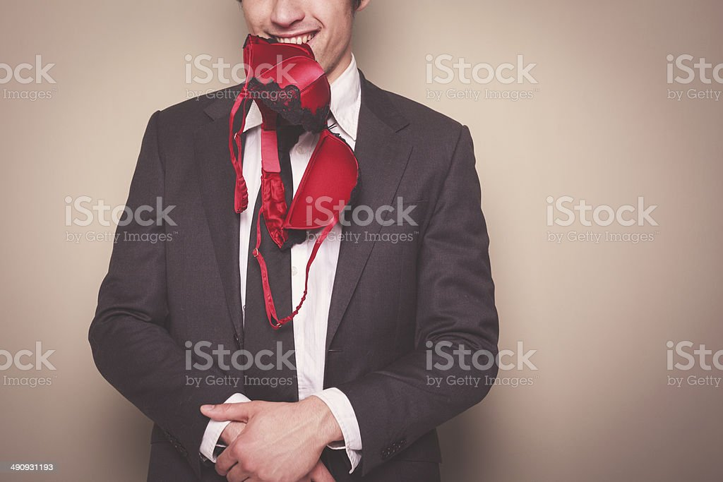 Businessman with bra in his mouth stock photo