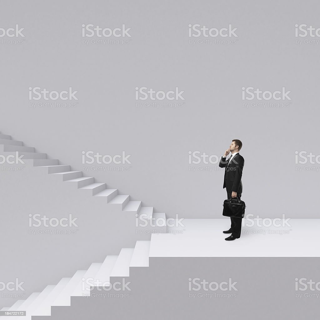 Businessman with briefcase faces up and down staircases royalty-free stock photo