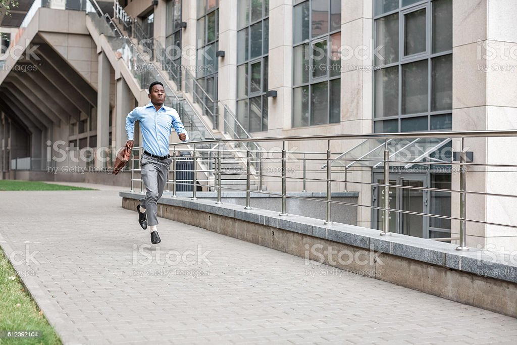 businessman with briefcase running stock photo