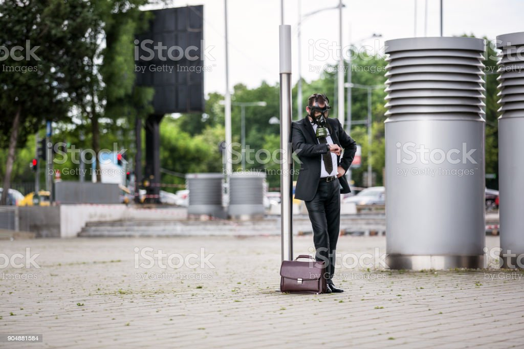 Businessman with briefcase wearing a gas mask looking to the watch. stock photo