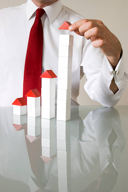 Businessman with building blocks to denote growth stock photo