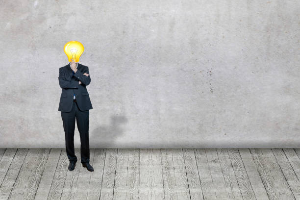 Businessman with bulb instead his head standing in front of the business concept stock photo