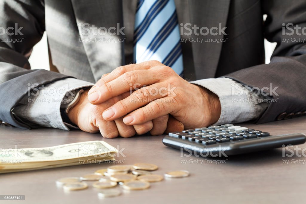 Businessman with calculator and dollar on table stock photo