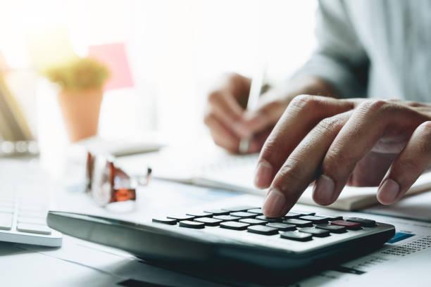 Geschäftsmann mit zählen machende Notizen griffbereit Büro-Rechner ist schreibt in einem Notizbuch – Foto