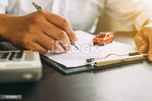 istock Businessman with car insurance contract and calculator. 1163896517