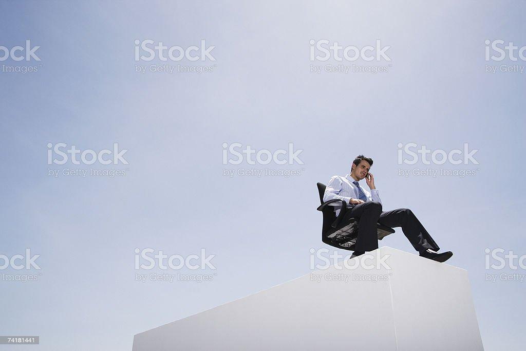 Empresário com telefone celular na Cadeira de Escritório na parede ao ar livre foto de stock royalty-free
