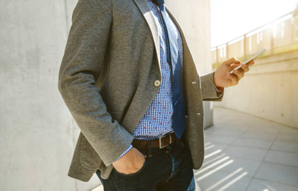 Businessman with cell phone Unrecognizable businessman with cell phone in front of a concrete wall blazer jacket stock pictures, royalty-free photos & images