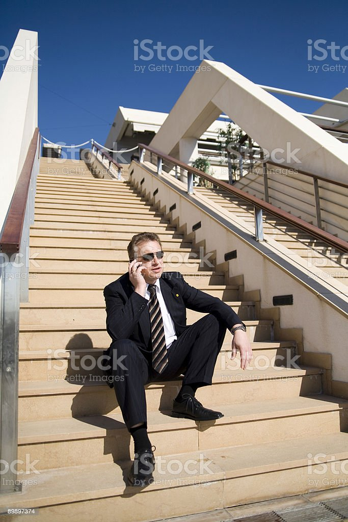 Businessman with cellular on the stairs royalty-free stock photo