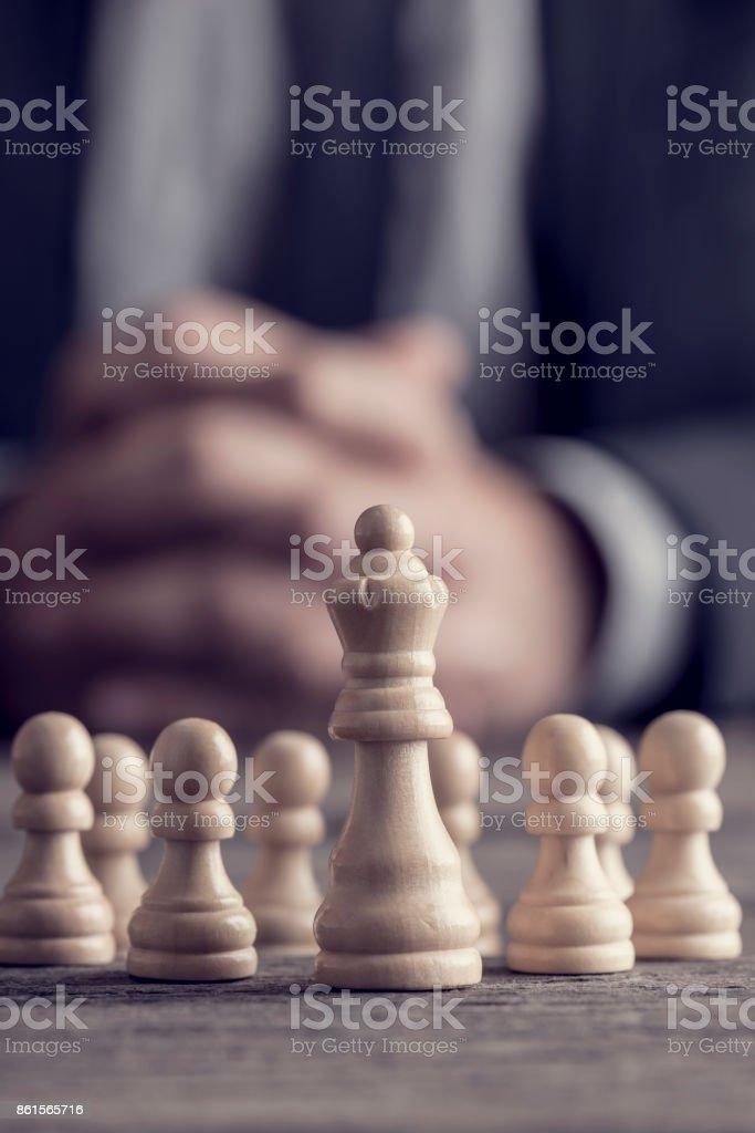 Geschäftsmann mit gefalteten Händen vor Königin Schachfigur unter Bauern sitzen – Foto