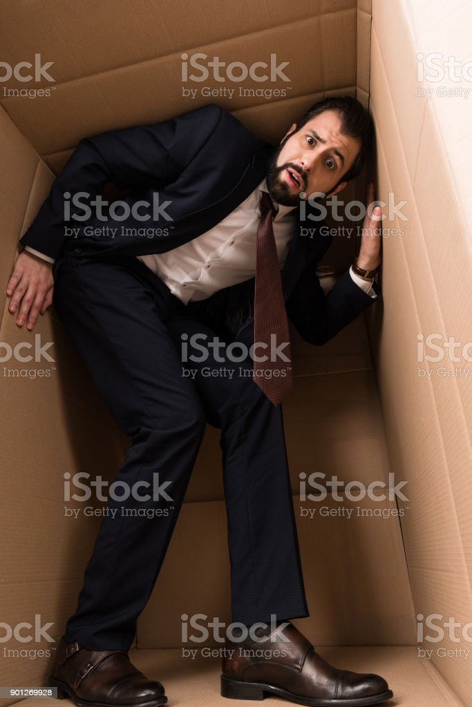businessman with claustrophobia inside a box stock photo