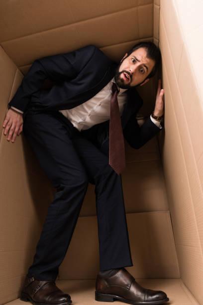 zakenman met claustrofobie in een doos - claustrofobie stockfoto's en -beelden